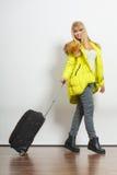 Lycklig ung kvinna i varmt omslag med resväskan Arkivbild
