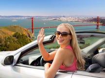 Lycklig ung kvinna i vinkande hand för konvertibel bil fotografering för bildbyråer