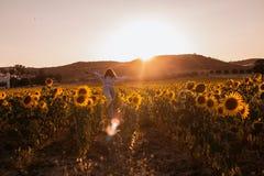 Lycklig ung kvinna med armar som öppnas från hennes tillbaka dans i ett solrosfält på solnedgången royaltyfri fotografi