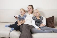 Lycklig ung kvinna med barn på hållande ögonen på TV för soffa Royaltyfria Bilder