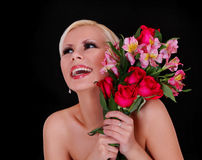 Lycklig ung kvinna med buketten av röda ro och rosa irises över svart bakgrund Fotografering för Bildbyråer