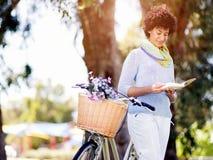 Lycklig ung kvinna med cykelläseboken Royaltyfri Fotografi