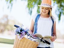 Lycklig ung kvinna med cykelläseboken Arkivfoton