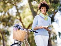 Lycklig ung kvinna med cykelläseboken Fotografering för Bildbyråer