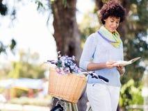 Lycklig ung kvinna med cykelläseboken Royaltyfria Bilder