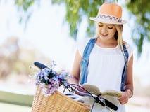 Lycklig ung kvinna med cykelläseboken Royaltyfri Bild