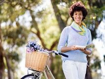 Lycklig ung kvinna med cykelläseboken Arkivbild