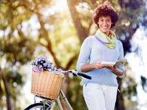 Lycklig ung kvinna med cykelläseboken Arkivfoto