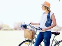 Lycklig ung kvinna med cykeln arkivbild