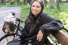 Lycklig ung kvinna med cykeln fotografering för bildbyråer