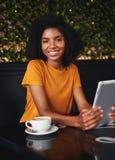 Lycklig ung kvinna med den digitala minnestavla- och kaffekoppen i kafé arkivbild