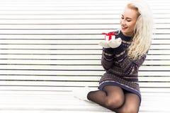 Lycklig ung kvinna med en gåva slitage vit vinter för härlig stående för begreppsklänningflicka Royaltyfria Bilder