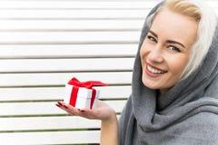 Lycklig ung kvinna med en gåva slitage vit vinter för härlig stående för begreppsklänningflicka Royaltyfri Foto