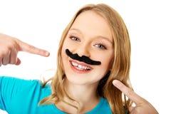 Lycklig ung kvinna med en mustasch Arkivbild