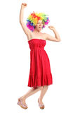 Lycklig ung kvinna med en peruk som gör en gest glädje Fotografering för Bildbyråer