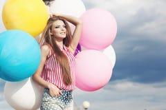 Lycklig ung kvinna med färgrika latexballonger royaltyfria foton