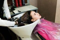 Lycklig ung kvinna med frisörtvagninghuvudet på hårsalongen royaltyfria foton