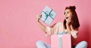 Lycklig ung kvinna med gåvor över rosa bakgrund royaltyfri bild