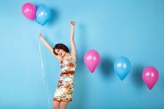 Lycklig ung kvinna med heliumluftballonger Arkivbilder