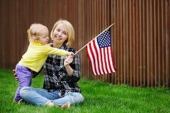 Lycklig ung kvinna med hennes hållande amerikanska flaggan för litet barnflicka Royaltyfri Foto