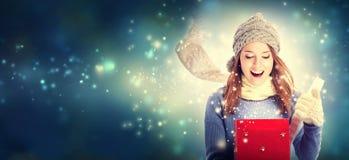 Lycklig ung kvinna med julklappasken Arkivbild