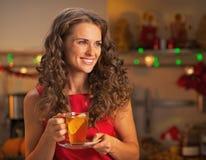 Lycklig ung kvinna med koppen av ljust rödbrun te som ser på kopieringsutrymme Royaltyfria Foton