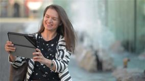 Lycklig ung kvinna med minnestavladatoren som har video pratstund, medan sitta på bänken på gatan, springbrunnbakgrund arkivfilmer