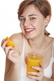 Lycklig ung kvinna med orange fruktsaft Arkivbild