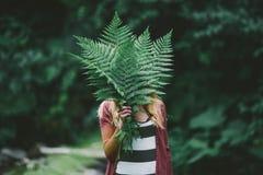 Lycklig ung kvinna, med ormbunkebladet i den gröna naturen Royaltyfri Foto