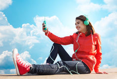 Lycklig ung kvinna med smartphonen och hörlurar Arkivbilder