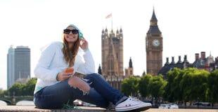 Lycklig ung kvinna med smartphonen och hörlurar Arkivfoton
