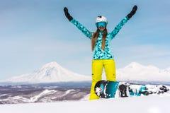 Lycklig ung kvinna med snowboarden som är främst av vulkan Arkivbild