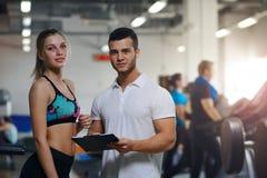 Lycklig ung kvinna och hennes personliga instruktör i idrottshall Royaltyfri Foto