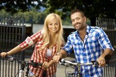 Lycklig ung kvinna och man med den utomhus- cykeln fotografering för bildbyråer