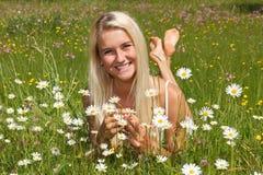 Lycklig ung kvinna på en blommaäng Royaltyfria Bilder