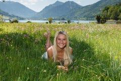 Lycklig ung kvinna på en blommaäng Royaltyfri Foto
