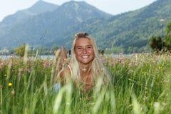Lycklig ung kvinna på en blommaäng Royaltyfri Bild