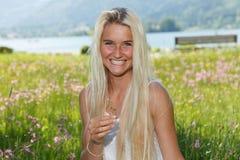 Lycklig ung kvinna på en blommaäng Royaltyfri Fotografi