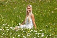 Lycklig ung kvinna på en blommaäng Fotografering för Bildbyråer