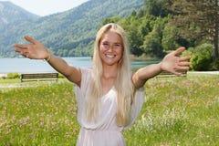 Lycklig ung kvinna på en blommaäng Arkivfoto