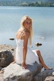Lycklig ung kvinna på en sjö i bergen Royaltyfria Bilder