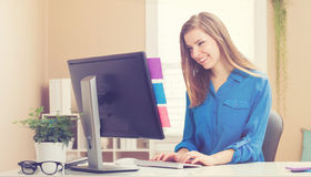 Lycklig ung kvinna på hennes dator i hennes inrikesdepartementet arkivfoton