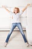 Lycklig ung kvinna på soffan fotografering för bildbyråer