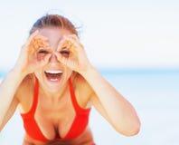 Lycklig ung kvinna på stranden som har gyckel arkivfoto