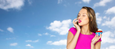 Lycklig ung kvinna som äter födelsedagmuffin Fotografering för Bildbyråer