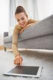 Lycklig ung kvinna som använder minnestavlaPC, medan lägga på soffan Royaltyfri Foto
