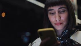 Lycklig ung kvinna som använder smartphonen, medan ridningspårvagnen, steadicam sköt l?ngsam r?relse lager videofilmer