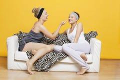 Lycklig ung kvinna som applicerar ansiktsmask på väns framsida, medan sitta på soffan mot den gula väggen Arkivfoton