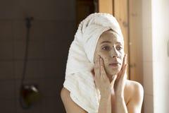 Lycklig ung kvinna som applicerar framsidamaskeringen i badrum Härlig fema Royaltyfria Bilder
