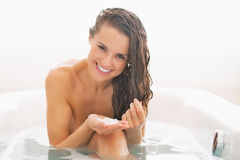 Lycklig ung kvinna som applicerar hårmaskeringen i badkar arkivbild